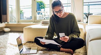 Een vrouw bekijkt papieren en checkt haar mobiele telefoon.
