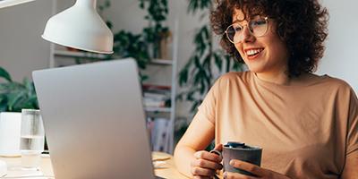 Op de afbeelding een jonge vrouw met een laptop.