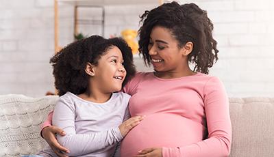 De afbeelding toont een zwangere vrouw en en een meisje samen op de bank